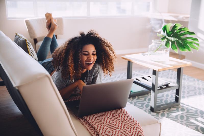 Woman laughing at laptop.